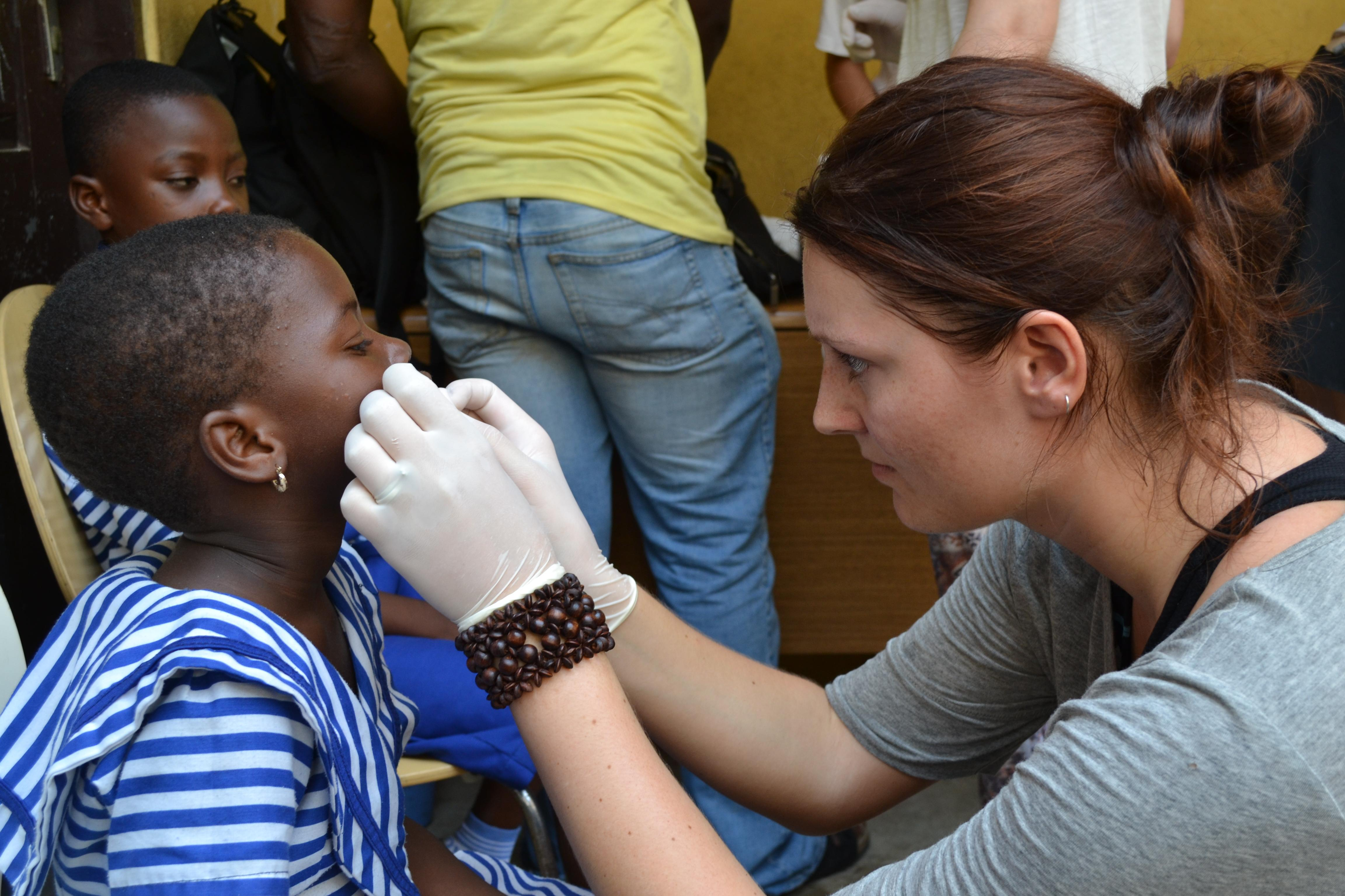 Child in Ghana is being treated on the face by a female healthcare intern at a medical outreach